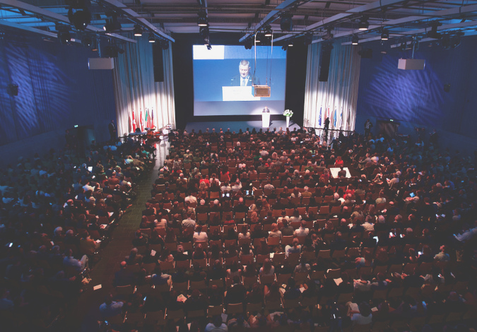 Photo of the crowded conference room and Federal Minister of Health Hermann Gröhe holding his opening speech