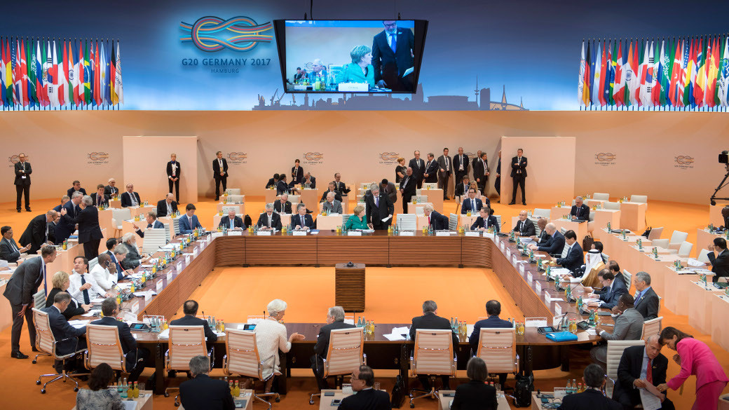 photo: view of the conference room at the G20 summit with state leaders sitting around the table and talking to each other before a meeting