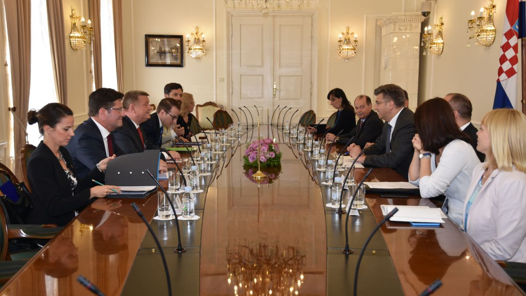Photo: Federal Minister of Health Hermann Gröhe, his Croatian counterpart and other persons attending the meeting are seated around a dark wooden table with microphones. The conference room has high white doors and walls with stucco ornaments and candela
